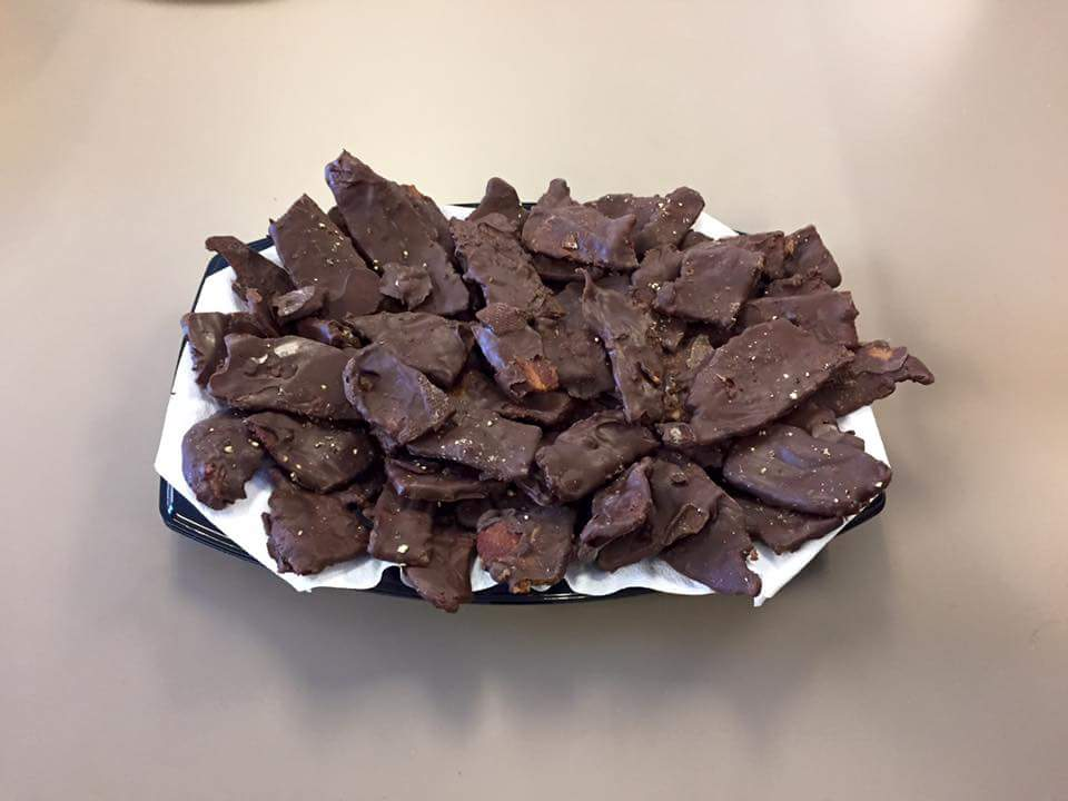 Photograph of a platter covered with chocolate covered bacon